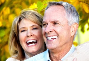 A headshot image of a happy old couple laughing outdoors.