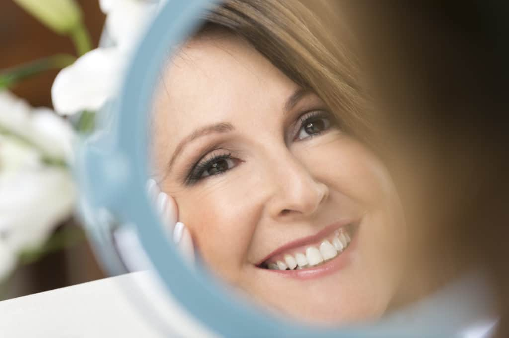 Happy mature woman looking in the mirror. Close-up of her porcleain veneers